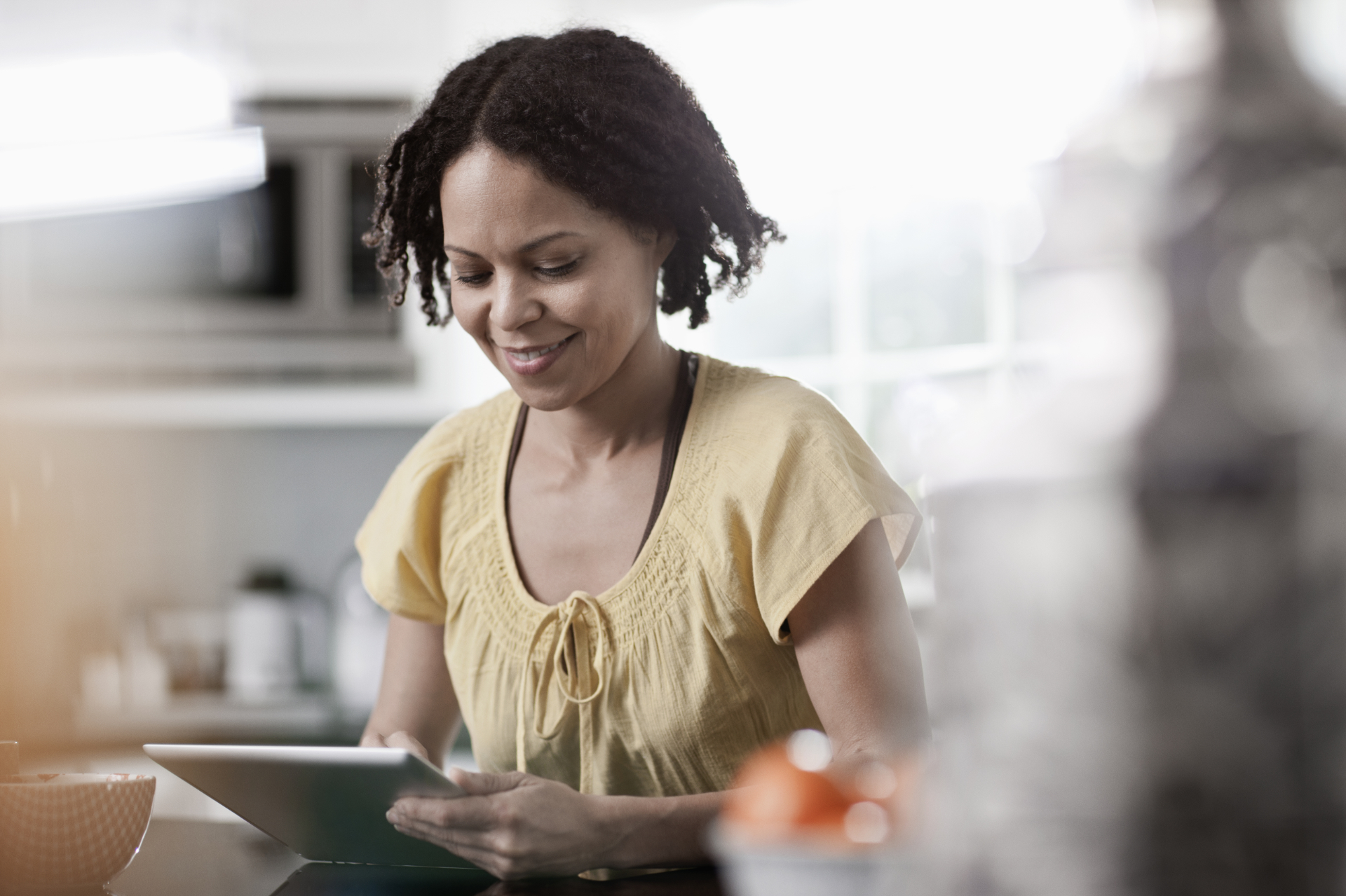 A woman using a digital tablet in her home. Standing in the kitchen.